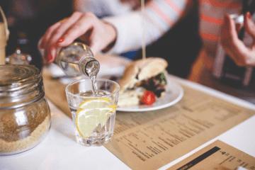 Ein gedeckter Tisch in einem Restaurant mit Speisekarte, MIneralwasser und Sandwich.