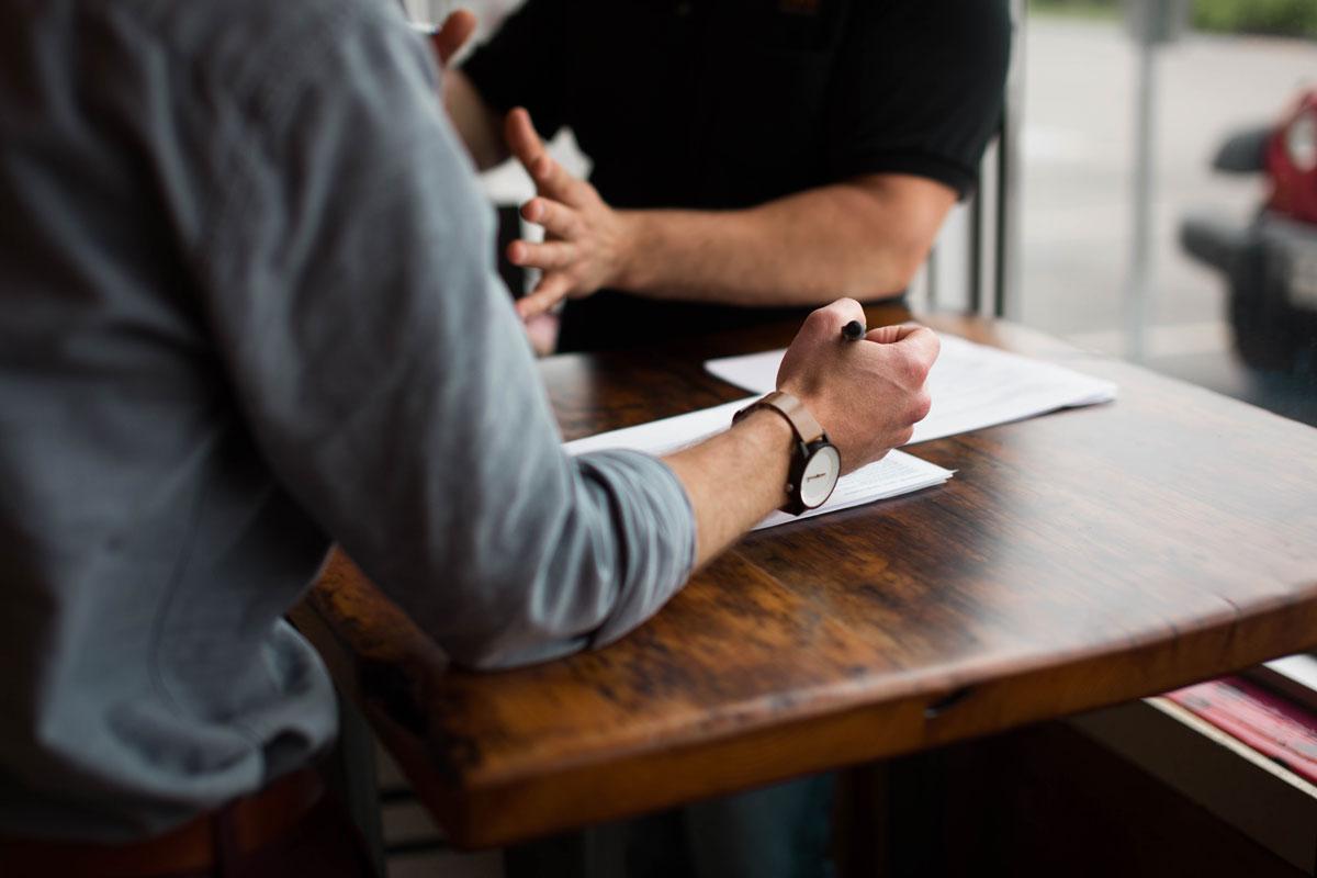 Zwei Gastronomen am Tisch mit Stift und Papier