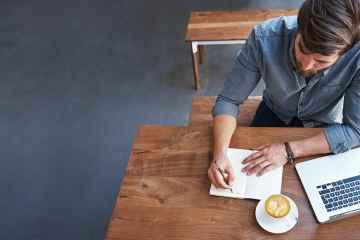 Ein männlicher Gastronom sitzt am Tisch mit Café, Laptop und Notizheft