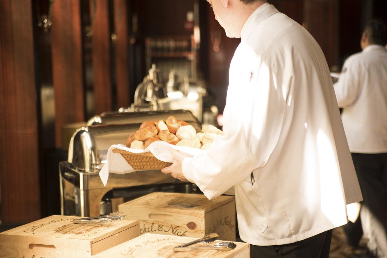 Ein Kellner bereitet mit seinen Händen Brot für das Frühstück vor