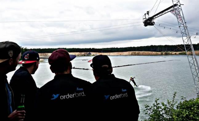orderbird-Mitarbeiter bestaunen Kollegen beim Wakeboarden auf dem Teamevent