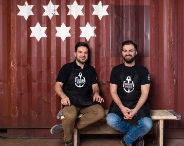 Die Gewinner des Deutscher Gastro-Gründerpreis und Gastro-Gründer von UNDERDOCKS lächeln zufrieden vor einem Container