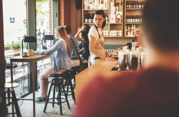 Eine Gastronomie-Mitarbeiterin in einem Café sieht sich verzweifelt um