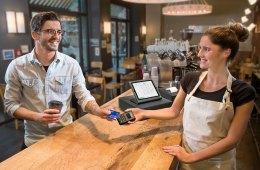 Ein Kunde bezahlt im Café mit seinem mobilen Endgerät