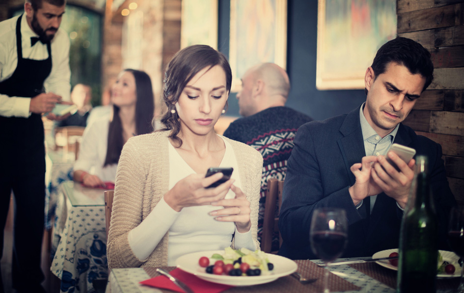 Ein Paar sitzt in einer Gastronomie und hat nur Augen fürs Handy