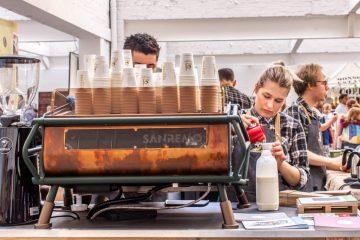 Barista steht an einer Kaffeemaschine