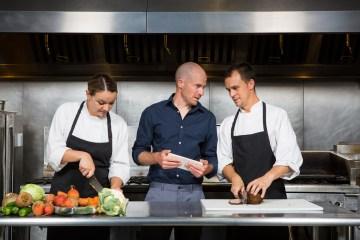 Ein Restaurantleiter schult seine Mitarbeiter in der Küche der Gastronomie