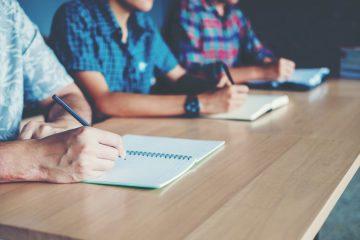 Prüfungssituation mit drei Personen am Tisch für die Befähigungsprüfung im Gastgewerbe