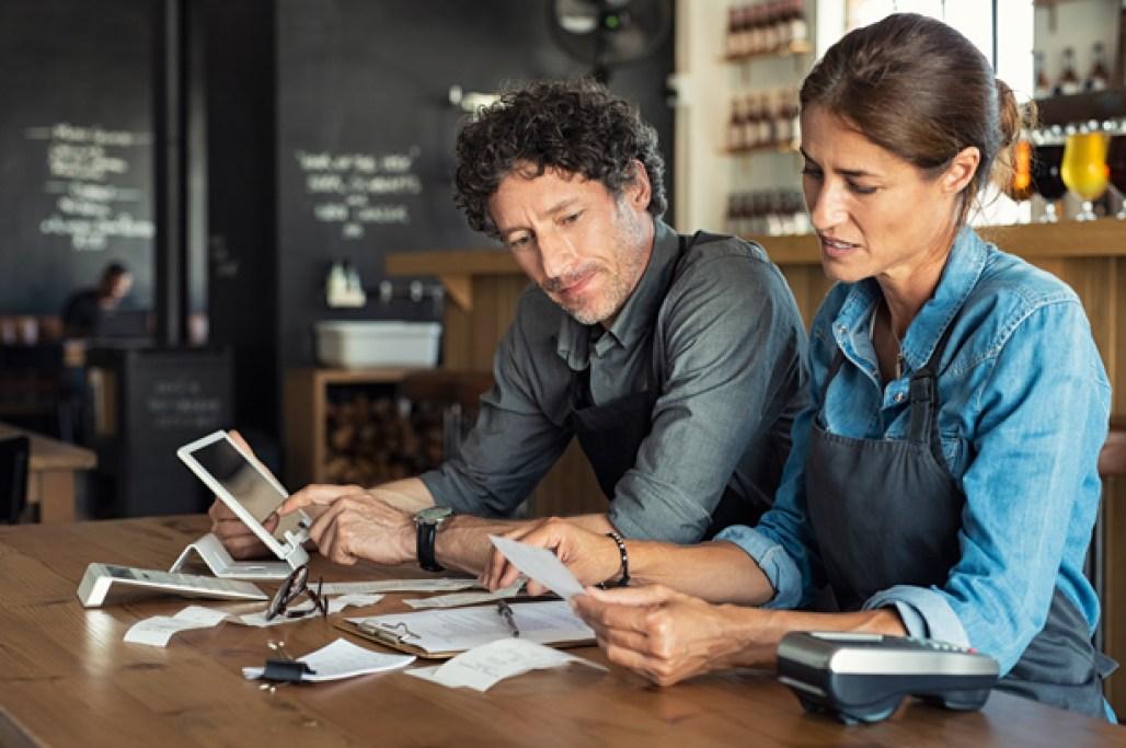 Ein Mann und eine Frau sitzen in ihrer Gastronomie und quälen sich mit ihrer Buchhaltung