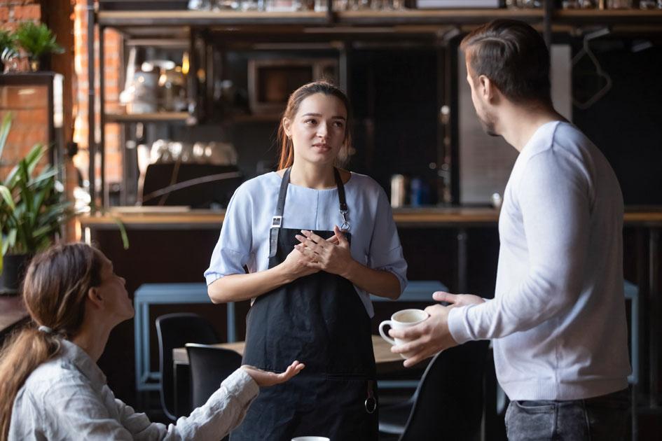 Junge Kellnerin die sich bei Kunden wegen der Belegausgabepflicht entschuldigt.