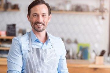 Ein lächelnder Gastronom hält eine GoBD konforme iPad-Kasse in der Hand