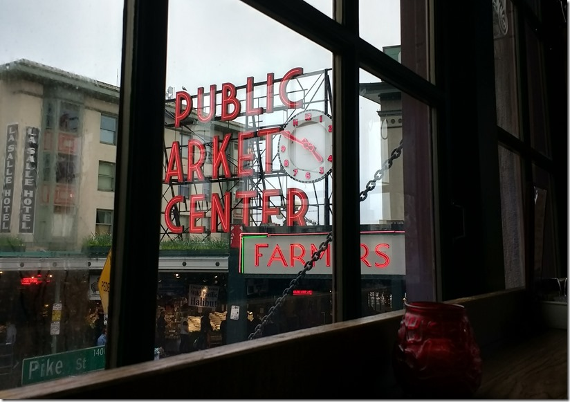 Public Market Center Sign and a clock and buildings on an overcast day