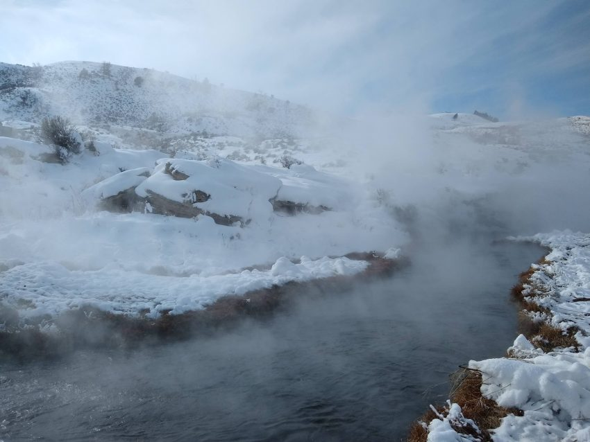 A steamy river passes through a snow covered valley