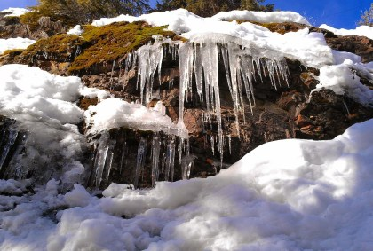 Big icicles hang from snowy rocks