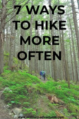 Two people walking on a trail through a green forest. They are looking up at the tall trees. Text reads: 7 ways to hike more often