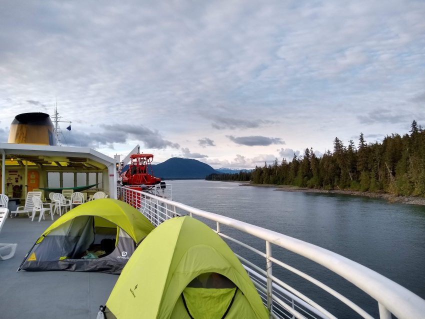 Alaska ferry upper deck with two tents and many deck chairs, passing through a narrow channel