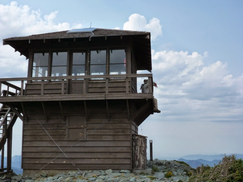 A brown wooden fire lookout tower on a pile of rocks. There are puffy clouds in a blue sky and distant mountains. Two people are sitting on the deck of the lookout tower on the Mt Fremont hike