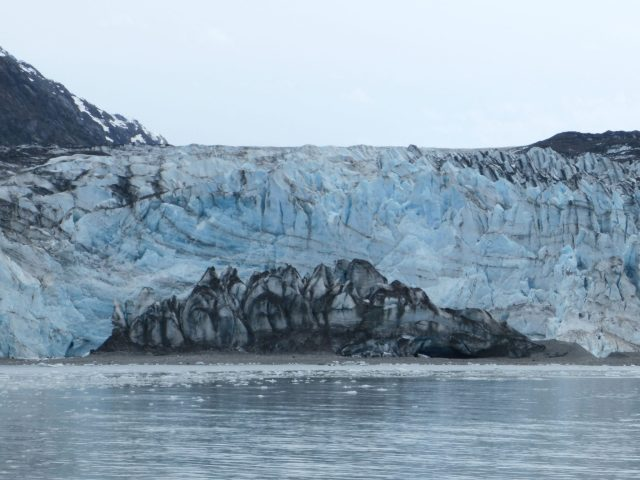 A glacier touches the sea in Glacier Bay. There is blue ice and in front of it the ice is gray and black where it is filled with rocks and gravel