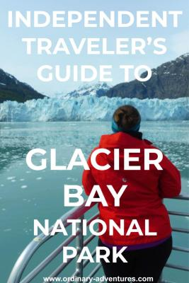A woman stands at the back of a boat facing away from the camera. She is looking at the blue ice of a glacier and mountains behind it. In the foreground there are lots of small pieces of ice in the water on a visit to Glacier Bay national park