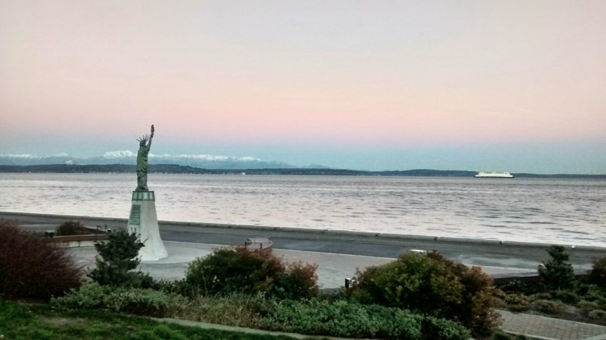 A small statue of liberty on Seattle's alki beach. It's dawn, the beach is empty and there are some shrubs and a trail. There are mountains and a ferry in the water in the background