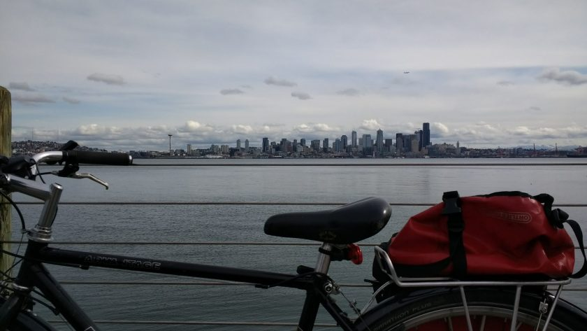 Outdoor activities in Seattle include cycling on the cities many trails. A plain black bike with a red back is in the foreground against a wire railing. There is gray water and gray sky. Across the water the Seattle skyline is visible, including the space needle