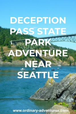 A high green metal bridge spans a narrow channel above blue water with several fishing boats and a sailboat passing under. Around the bridge and water are rocky headlands and forested hillsides. It's a blue sky sunny day. Text reads: Deception Pass State Park adventure near Seattle