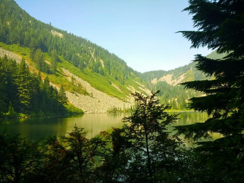 Talapus lake hike near Snoqualmie pass. It's a large alpine lake surrounded by forest and rocky mountains, which are reflected in the lake. There are evergreen trees in the foreground and it's a sunny day