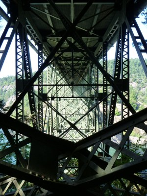 The underside of a metal bridge is a maze of metal going in many directions
