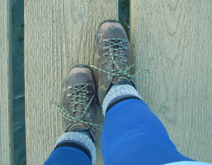 Two worn hiking boots seen from the person wearing them. A person's lower legs with blue leggings and gray and blue socks are also visible. The person is standing on a wooden path