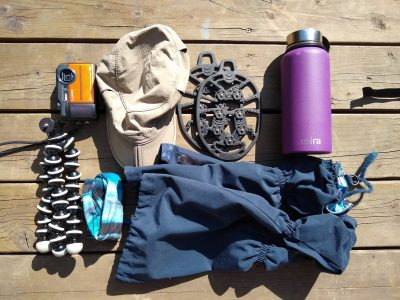 Extra day hiking gear on a wooden deck, including a camera, tripod, hat, gaiters, rubber ice grippers for shoes and a purple water bottle