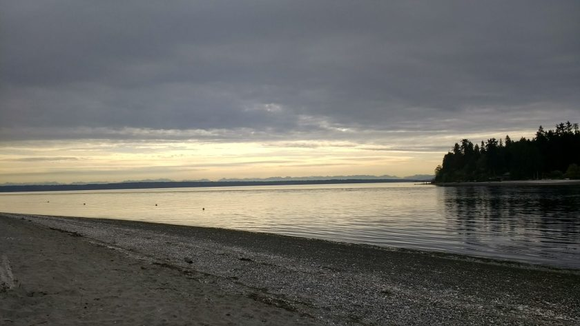A gravel and sand beach on an overcast day at sunrise. There is a narrow passage of water with forested land across it. In the distance there are mountains beneath the clouds