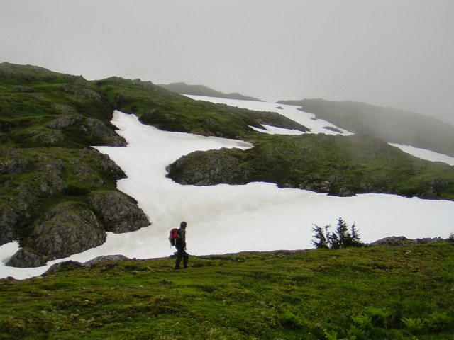 Patches of snow cover a rocky mountain on a foggy day. A person is standing on a grassy area walking across it