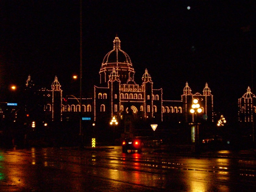 The British Columbia parliament buildings are light up at night. Small white lights outline the details of the building.