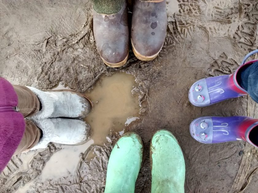 Four pairs of boots around a mud puddle.