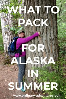 A women wearing gray pants and a long sleeved purple shirt is hugging an old growth tree next to a trail. She also has a blue backpack and a beige hat. Text reads: what to pack for alaska in summer