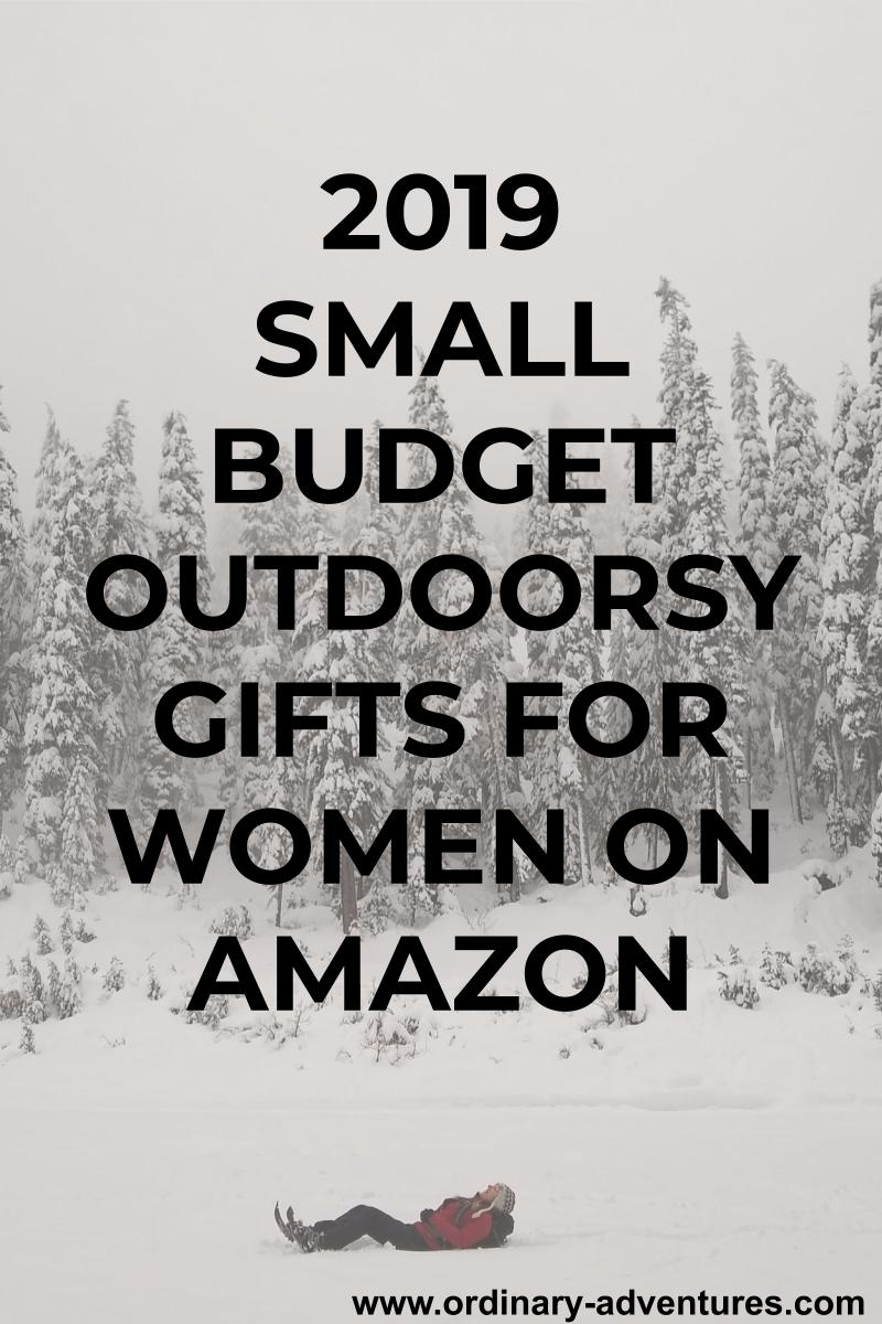 An overcast day with a snowfield in the foreground and snowy evergreen trees in the background. A person in laying on the ground in the field looking up at the sky. Text reads: 2019 small budget outdoorsy gifts for women on amazon