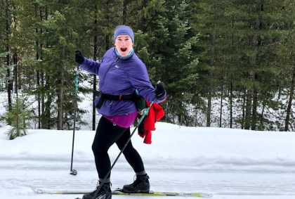 A woman on cross country skis making an excited, goofy face at the camera. She is wearing a blue headband, a purple jacket and black leggings and boots. She has a fanny pack with a red jacket attached to it.