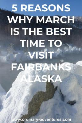 A hot springs pool is surrounded by rocks covered in snow. There is steam coming up from the pool. There are a few log buildings nearby and the area is surrounded by forested hills. Text reads 5 reasons why March is the best time to visit Fairbanks Alaska