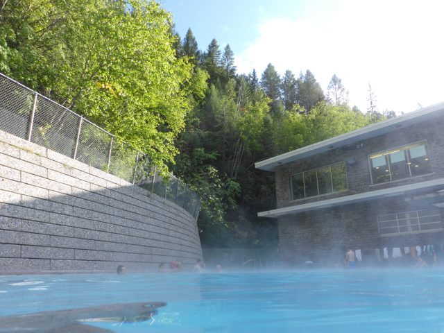 A hot springs pool at Radium Hot springs in Kootenay National Park with a wall on one side and a building on the other. The pool area is surrounded by trees on the hillside above