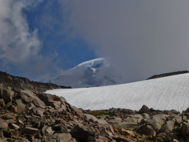 A part of Mt Rainier is visible behind the clouds in an otherwise blue sky above a rock and snow field