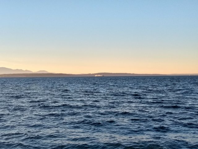Blue water at sunset on a sunny day. A ferry crosses the water in front of islands and mountains as seen from Alki beach, one of the most beautiful walks in seattle