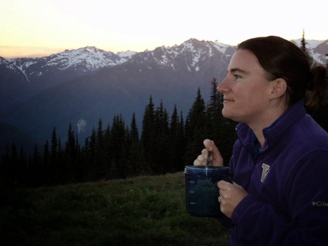 A woman wearing a fleece is holding a mug and eating out of it. She is smiling and looking out at the sunset at Hurricane Ridge picnic area in Olympic National Park