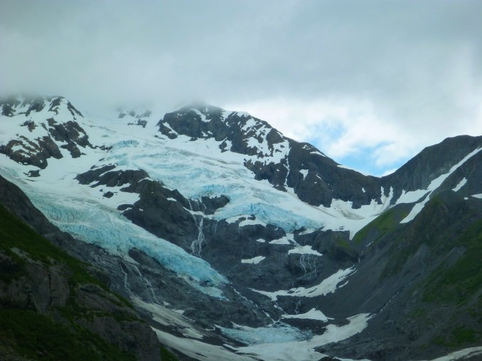 Two hanging glaciers in high mountain valleys. They are between high snow covered mountains on an overcast day above a green valley floor