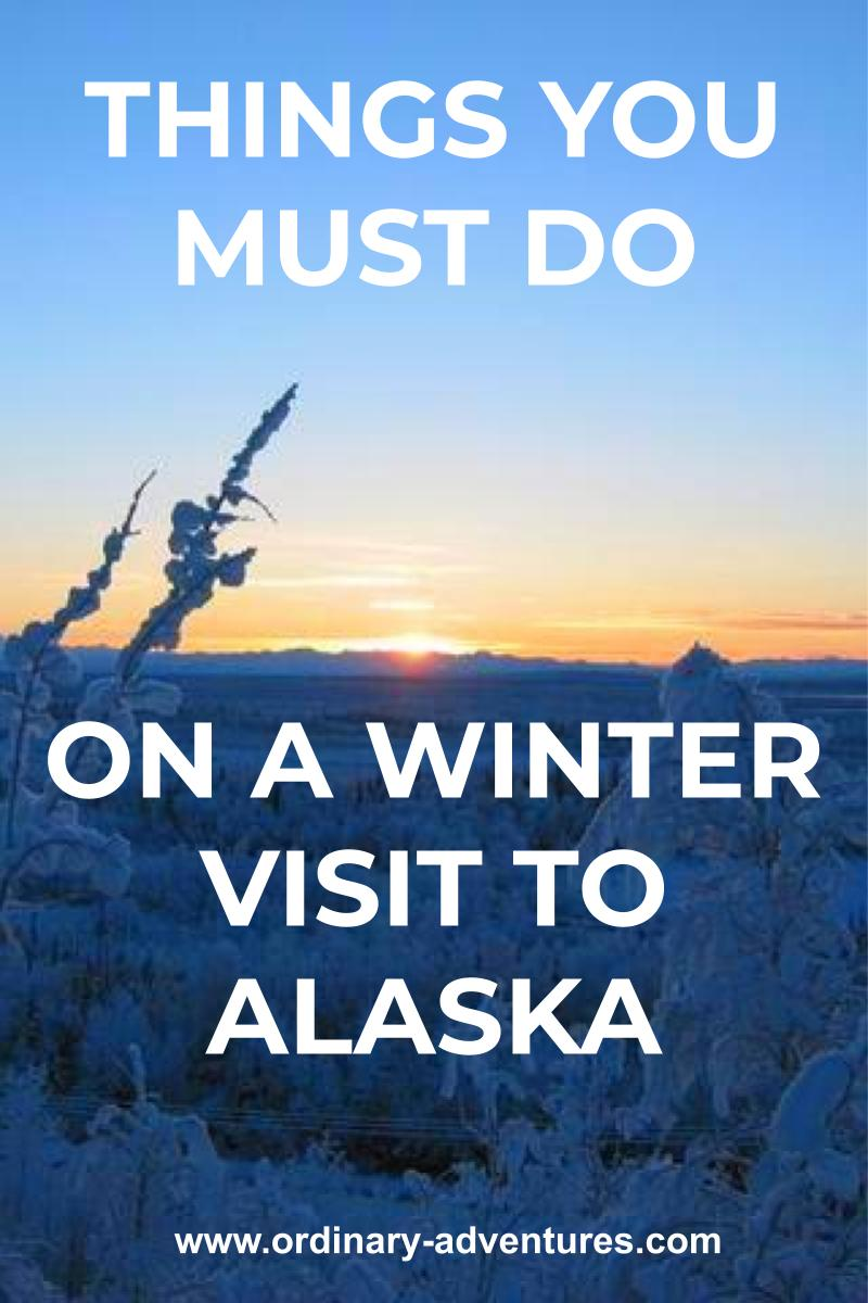A sunset behind distant mountains with snowy small trees in the foreground. Text reads: Things you must do on a winter visit to Alaska