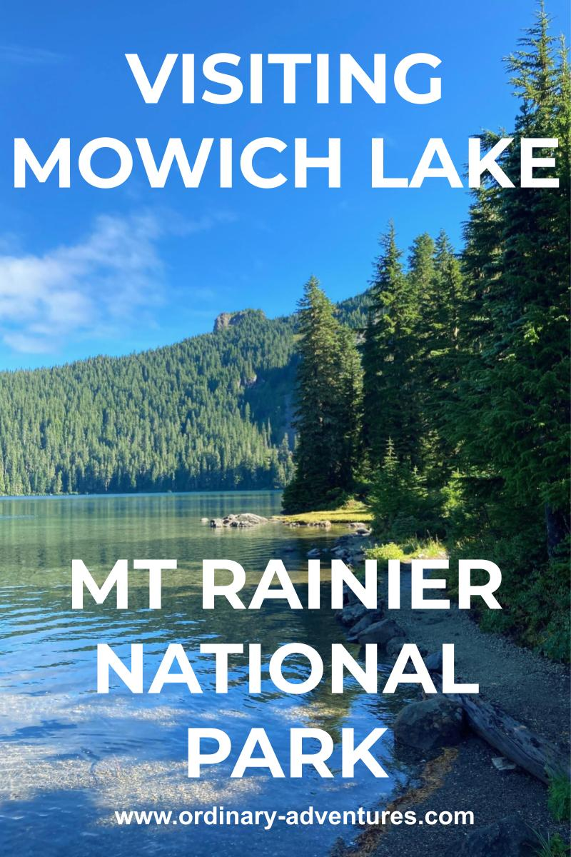 A clear alpine lake shore surrounded by evergreen trees on a sunny day. There are more forested hillsides across the lake. Text reads: visiting Mowich Lake Mt Rainier National Park
