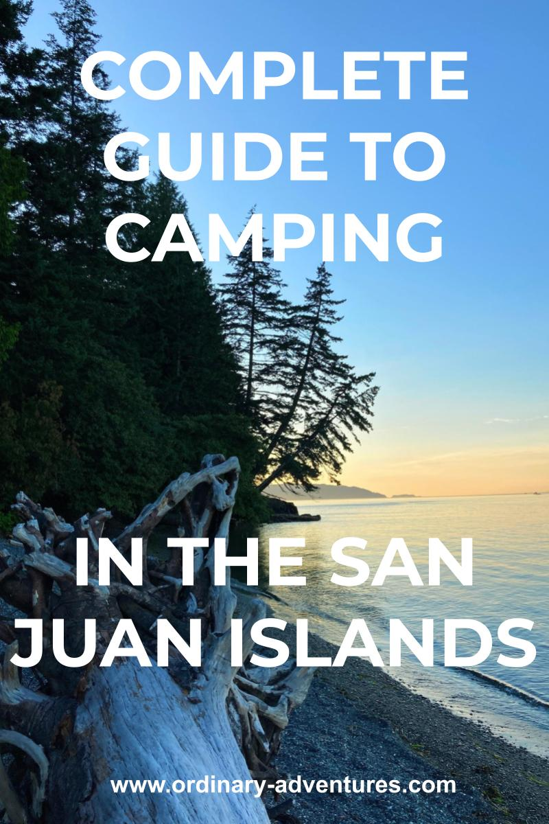 The sun has just set behind a forested island. There are tall trees against the pale blue sky. There is some pink and orange sunset light on a distant island. There is a piece of driftwood on the beach in the foreground. Text reads: Complete guide to camping in the san juan islands