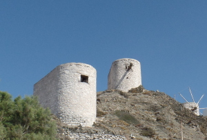 Remnants of the past, old windmills, used to grind grain, stand on the hillside.