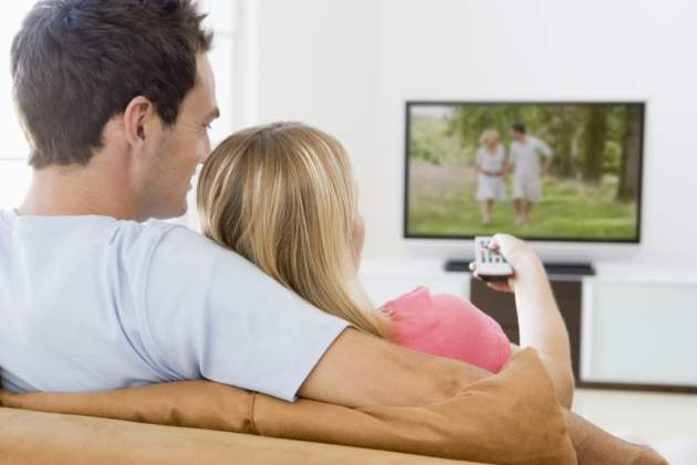 Couple in living room watching television