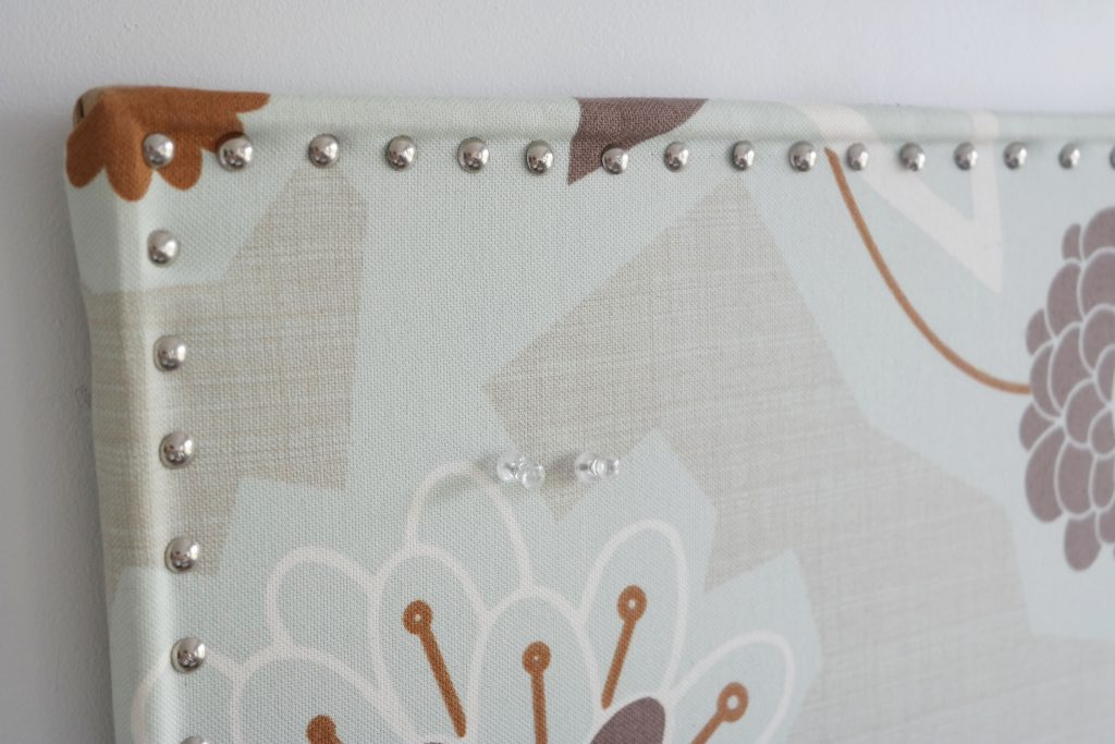 Fabric covered bulletin board nail heads