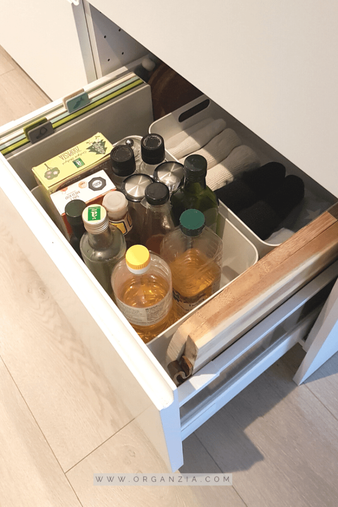 Kitchen towels/oils/chopping boards organized in kitchen drawers